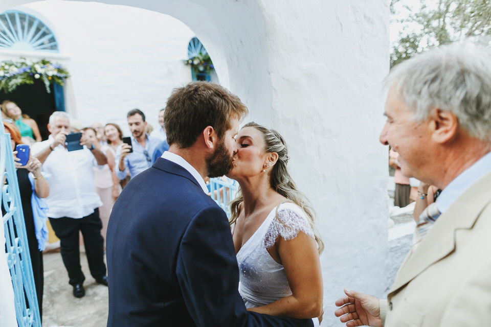 Bride and grooms kiss in front of church