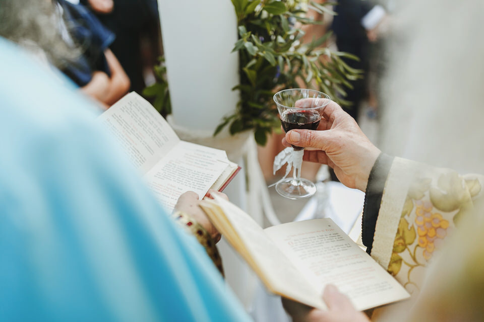 The priest is holding the wine